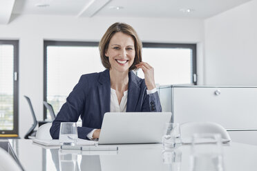 Portrait of smiling businesswoman using laptop at desk in office - RORF01350