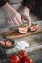 Woman's hands preparing Caprese Salad, partial view - ALBF00528