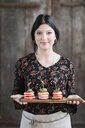 Portrait of smiling woman serving Caprese Salad - ALBF00534