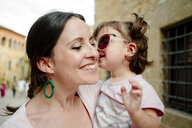 Happy baby girl wearing mother's sun glasses and kissing her - GEMF02090