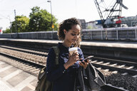 Young woman at train station reading text messages on her phone - UUF14165