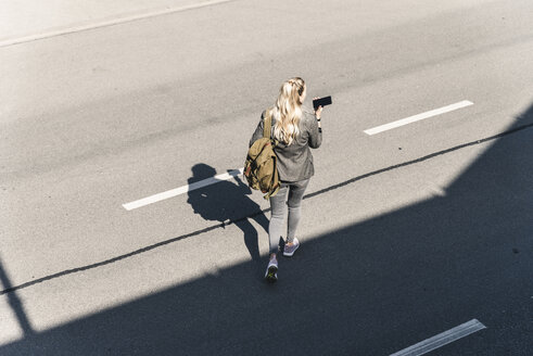 Young woman walking on empty road, talking into her smartphone - UUF14171