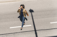 Young woman walking on empty road, wearing headphones, listening music - UUF14174