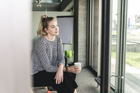 Young woman sitting in office, taking a break, drinking coffee - UUF14180