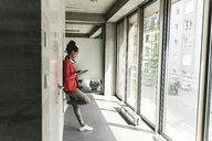 Young woman with headphones standing in corridor, using digital tablet - UUF14219