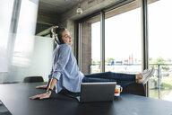 Young businesswoman sitting on desk, listening music - UUF14225