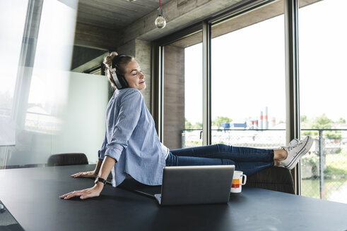 Young businesswoman sitting on desk, listening music - UUF14225