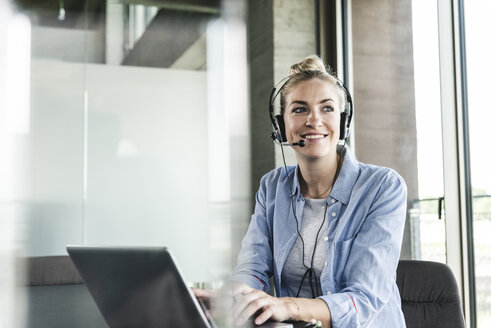 Young businesswoman sitting at desk, making a call, using headset and laptop - UUF14231