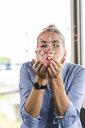 Happy businesswoman blowing confetti, celebrating success - UUF14237