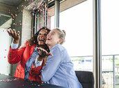 Young busniesswomen celebrating success, throwing confetti - UUF14240