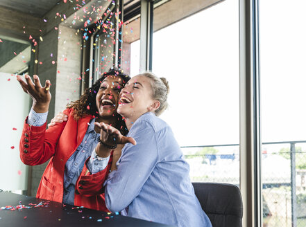 Young busniesswomen celebrating success, throwing confetti - UUF14240