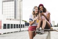 Best friends with skateboard, having fun together, listening music - UUF14258