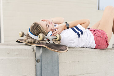 Young woman with skateboard, listening music - UUF14264