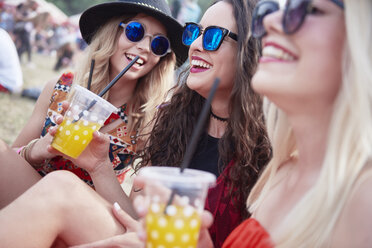 Friends drinking juice and sitting on meadow during music festival - ABIF00598