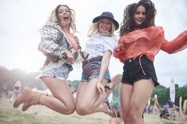 Happy friends jumping during music festival - ABIF00610