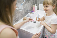 Mother and daughter brushing teeth in bathroom - AWF00067