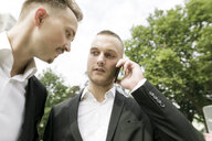 Two young businessmen with cell phone outdoors - KMKF00380