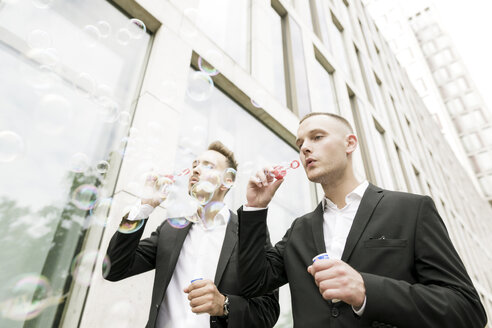 Two young businessmen blowing soap bubbles outdoors - KMKF00383