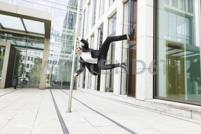 Young businessman wearing headphones jumping at lamp post in the city - KMKF00386 - Katharina Mikhrin/Westend61