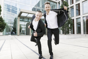 Two happy businessmen in front of office building - KMKF00389