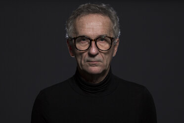 Portrait of serious senior man wearing glasses in front of dark background - AWF00094