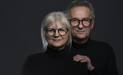 Portrait of senior couple wearing glasses in front of dark background - AWF00097