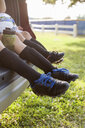 Legs and feet of boy and younger sister sitting in car boot wearing football boots - ISF12682
