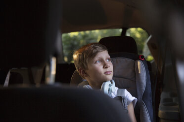 Boy in car back seat gazing out through window - ISF12688