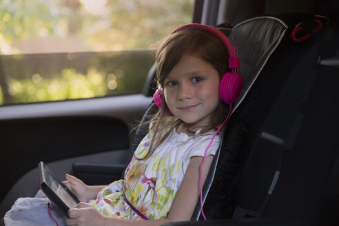 Portrait of girl wearing pink headphones and using digital tablet in car - ISF12691