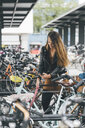Young woman with bicycle using cell phone in the city - KNSF03986