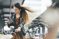 Young woman with bicycle using cell phone in the city - KNSF03989