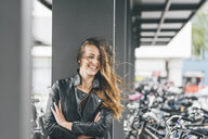 Portrait of happy young woman at bicycle parking station in the city - KNSF03992
