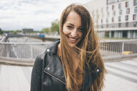 Portrait of smiling young woman with windswept hair on motorway bridge - KNSF03998