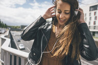 Smiling young woman listening to music on motorway bridge - KNSF04001