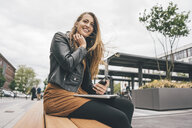 Young woman with laptop and cell phone in the city - KNSF04004