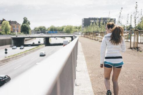 Sportive young woman walking beside motorway - KNSF04028