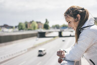 Sportive young woman looking on watch at motorway - KNSF04031