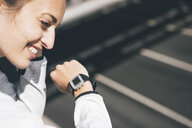 Smiling sportive young woman outdoors with watch - KNSF04034