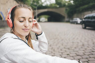 Smiling sportive young woman with closed eyes wearing headphones outdoors - KNSF04037