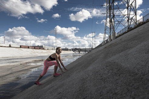 Female runner moving up steep river aqueduct, Los Angeles, California, USA - ISF12733