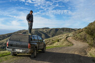 Man looking down from top of pick up truck, Big Sur, California, USA - ISF12772
