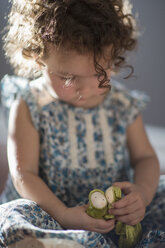 Young girl, sitting on floor, playing with toy - ISF12871