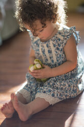 Young girl, sitting on floor, playing with toy - ISF12874