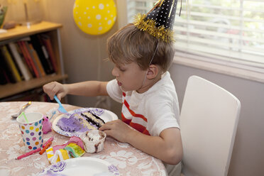 Boy in party hat sitting at table eating birthday cake - ISF12901