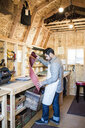 Leather craftsman selecting red leather from box in workshop - ISF12913