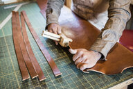 Hands of leather craftsman using wooden clamp on workshop bench - ISF12916
