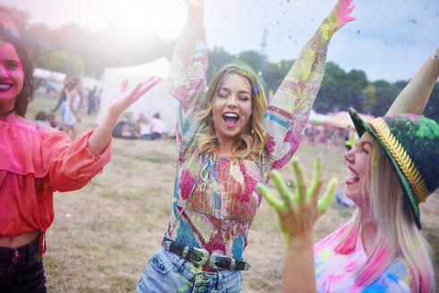 Friends dancing during music festival, colour powder - ABIF00618