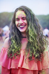 Portrait of young woman with colour powder at music festival - ABIF00627