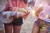 Women having fun with sparklers at music festival - ABIF00630