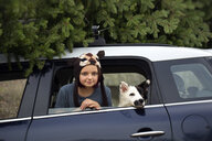 Girl with dog leaning out of car window - ISF13048